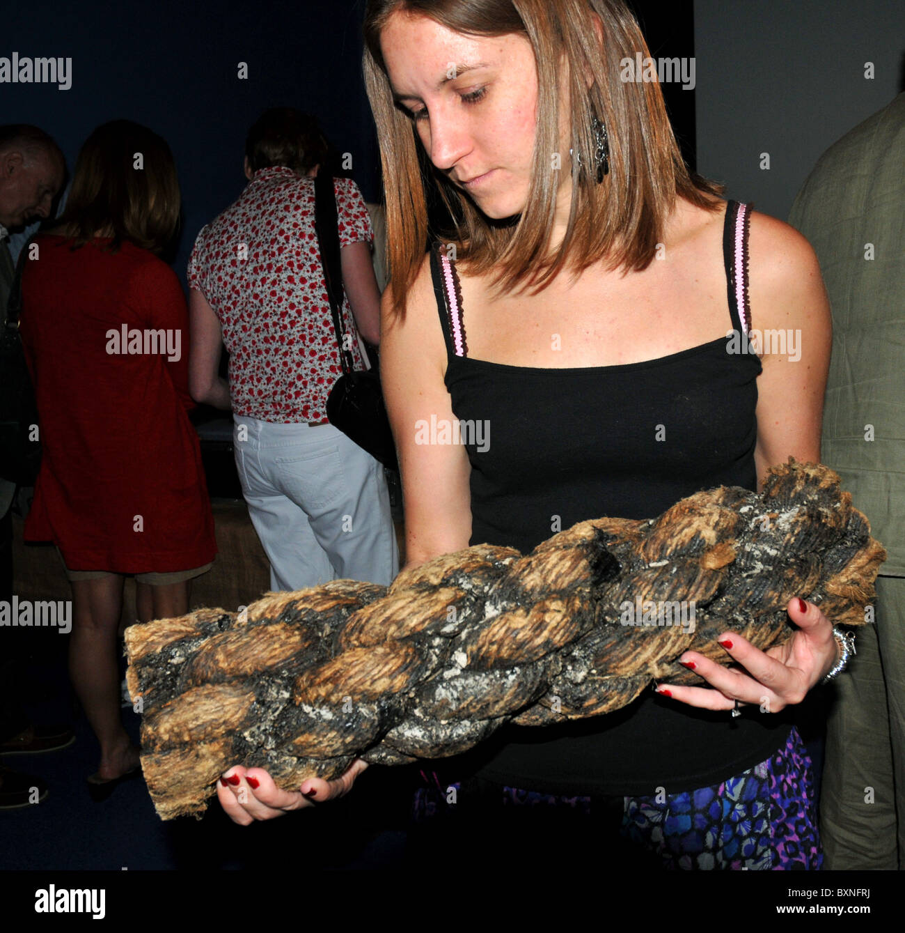 Visitor holding a sample of preserved rope from the wreck at The Mary Rose Museum. Portsmouth, Hampshire, Britain, - Stock Image