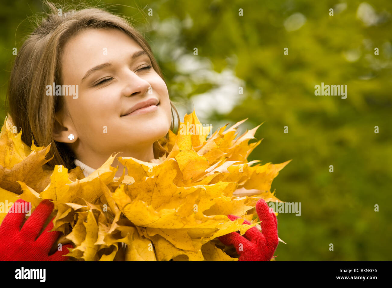 dada7698ea Photo of smiling girl with closed eyes wearing maple garland around her  neck - Stock Image