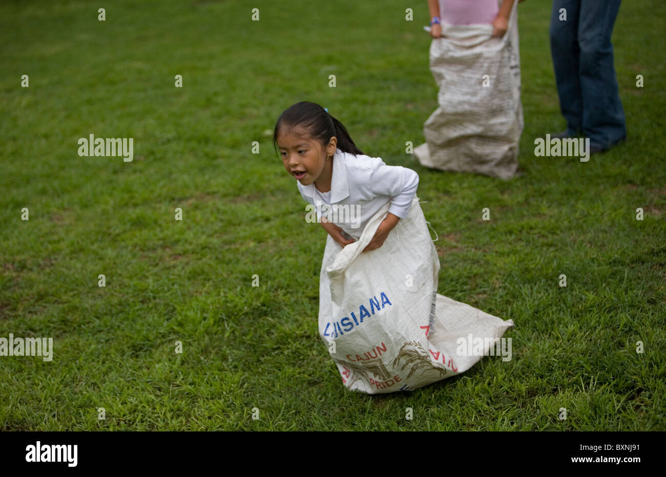A girl participates in a running sack race during summer camp at a horse therapy center in Mexico City, July 29, - Stock Image