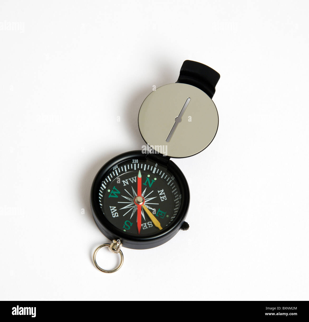 Travel, Navigation, Map Reading, Sighting compass with dial pointing to magnetic north on a white background. Stock Photo