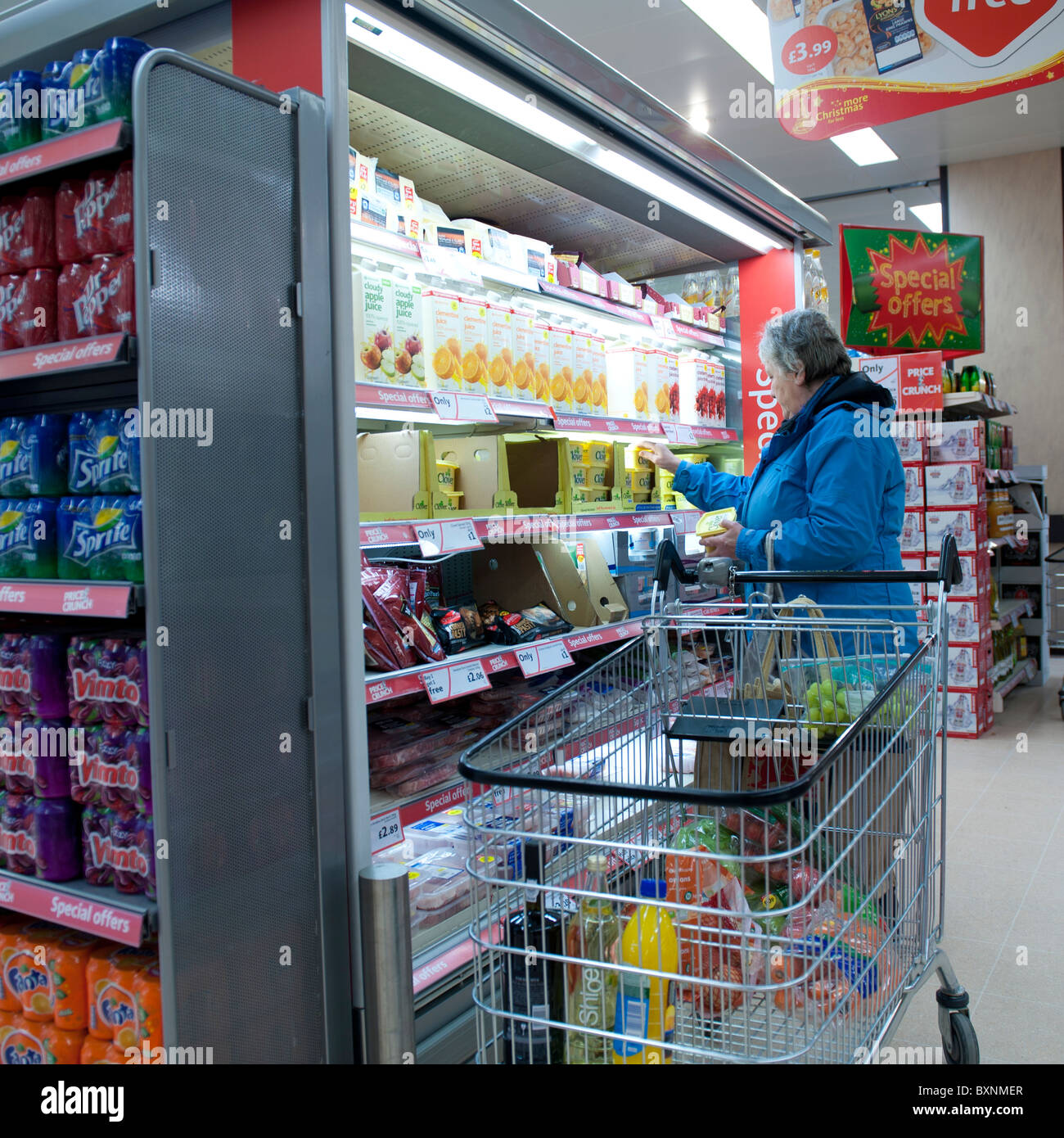 A woman with a trolley shopping for food in a branch of the Morrissons supermarket, UK - Stock Image