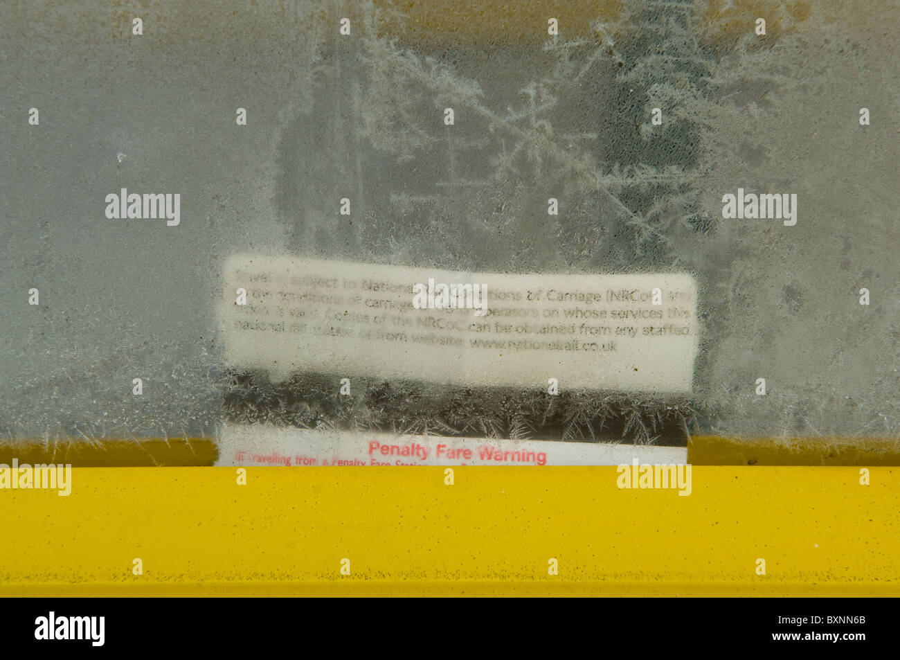 Discarded rail ticket trapped behind a frosted glass window. - Stock Image
