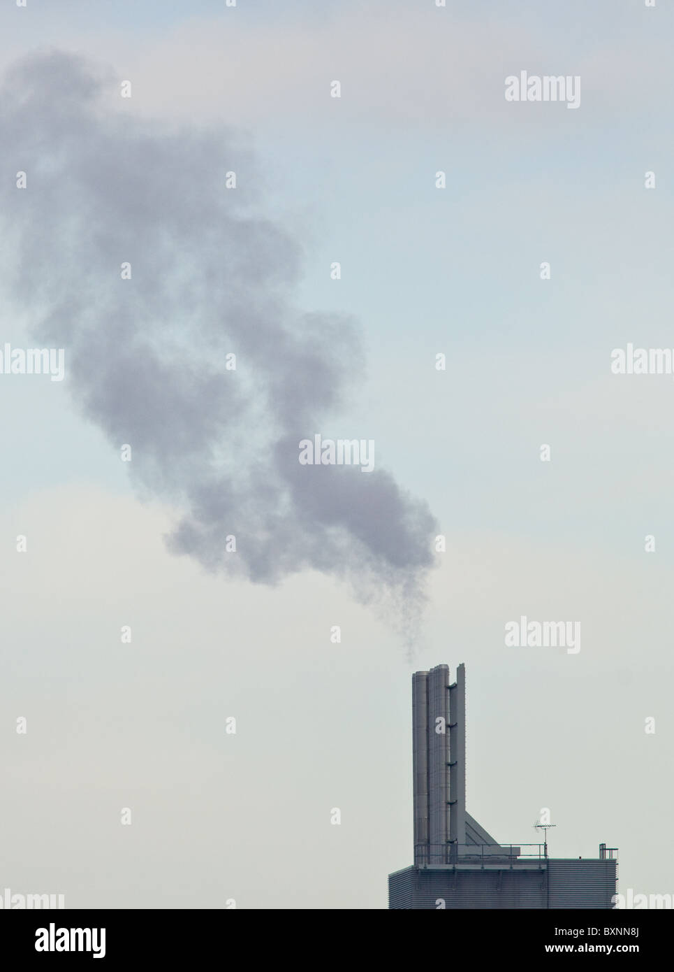 Steam and hot exhaust gases being emitted through steel chimneys - Stock Image