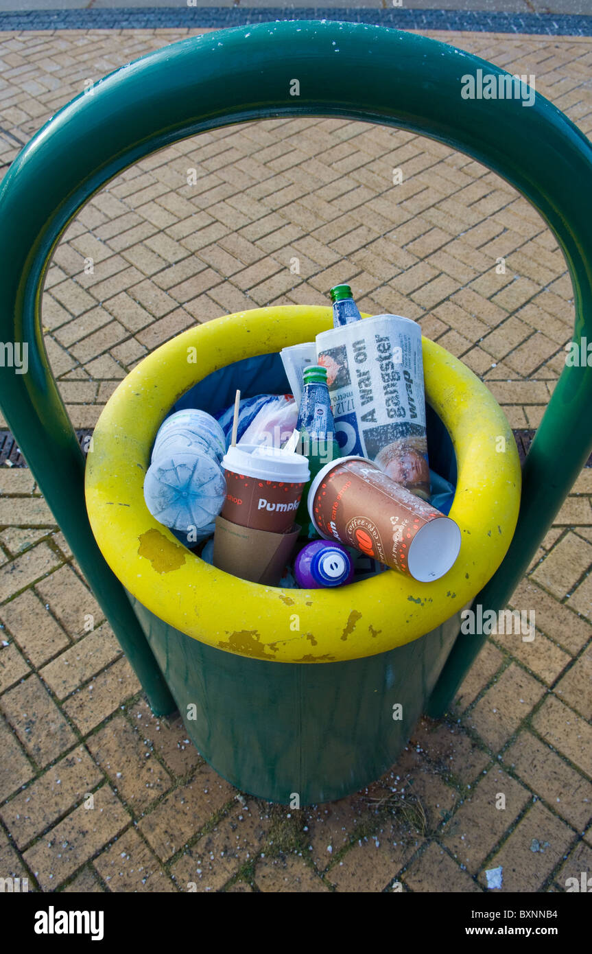 Railway station platform waste bin full with recyclable waste, paper cups, plastic bottles and newspaper. - Stock Image