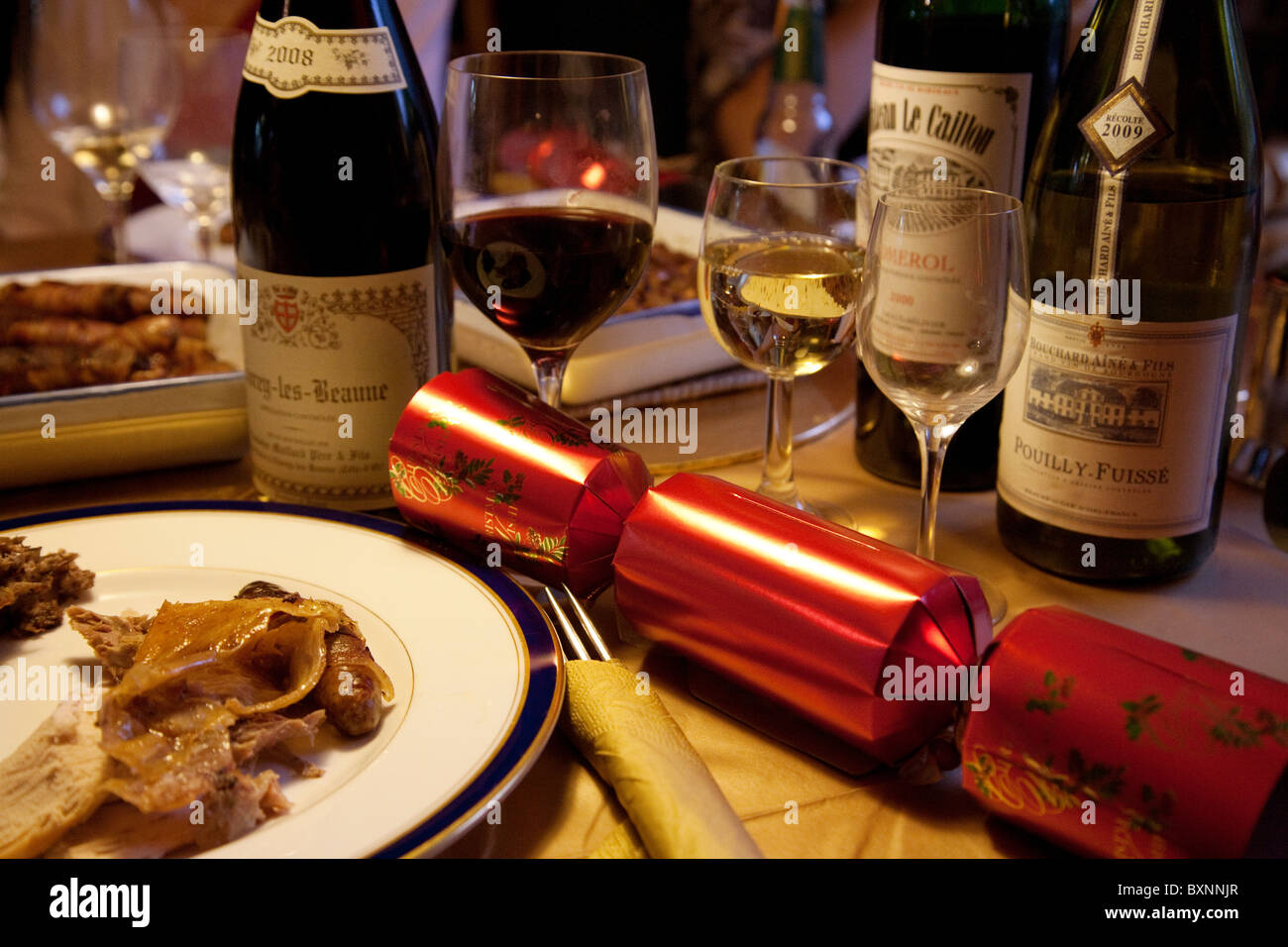 Christmas dinner table place setting with Xmas cracker and red and white wines, UK - Stock Image