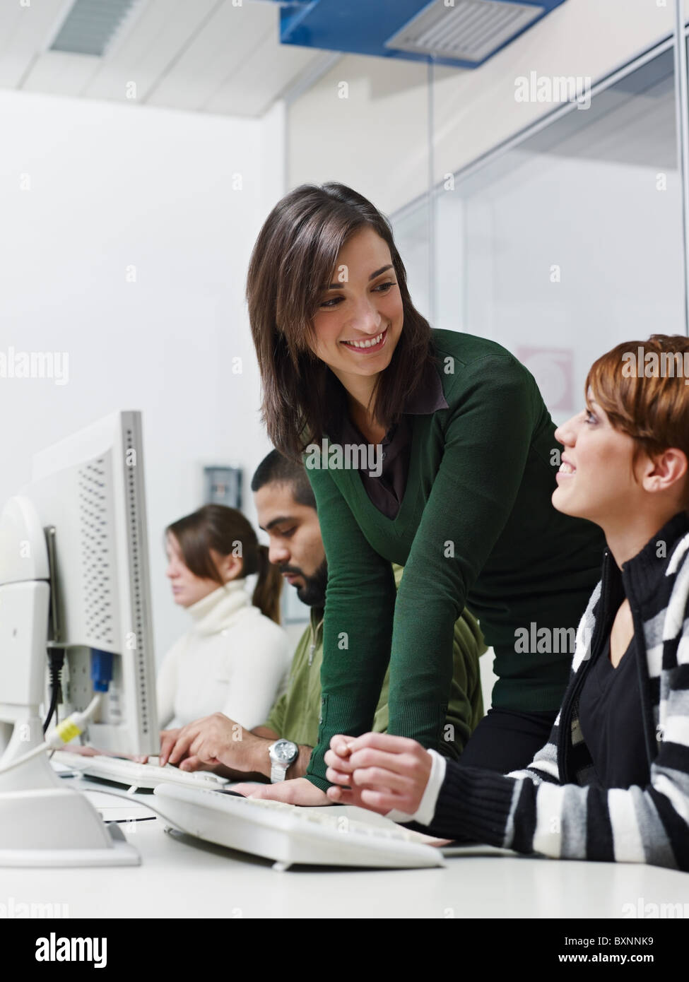 Computer class with caucasian female teacher helping student. Vertical shape, side view, waist up - Stock Image