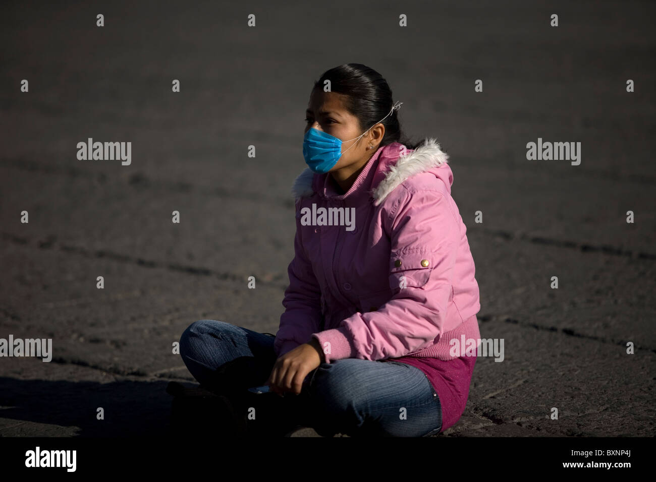 A young woman wearing a mask as a precaution against swine flu sits in Mexico City's main Zocalo square, May - Stock Image