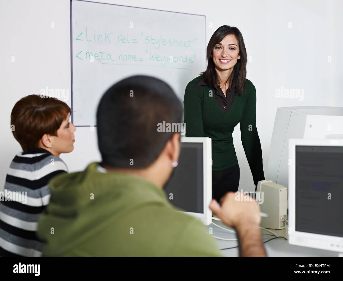 Computer class with caucasian female teacher talking to hispanic student. Horizontal shape, focus on background - Stock Image