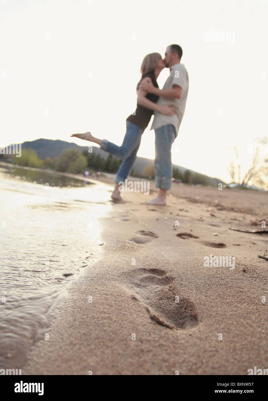 modern couple kissing each other on beach with footprints in sand Stock Photo