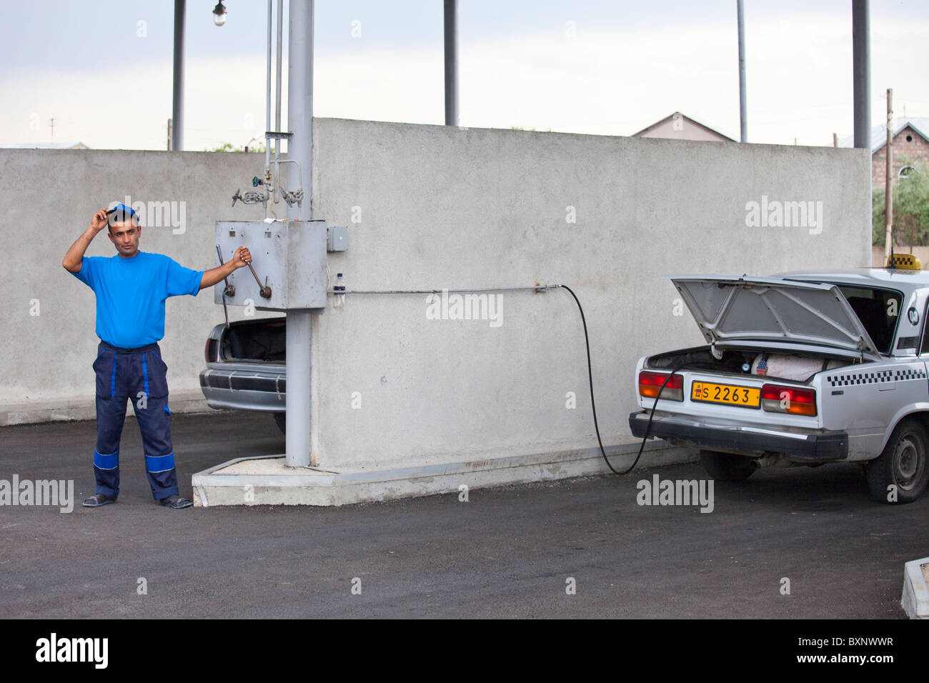 Attendant stands aside for saftey, CNG, compressed natural gas station in Yerevan, Armenia - Stock Image