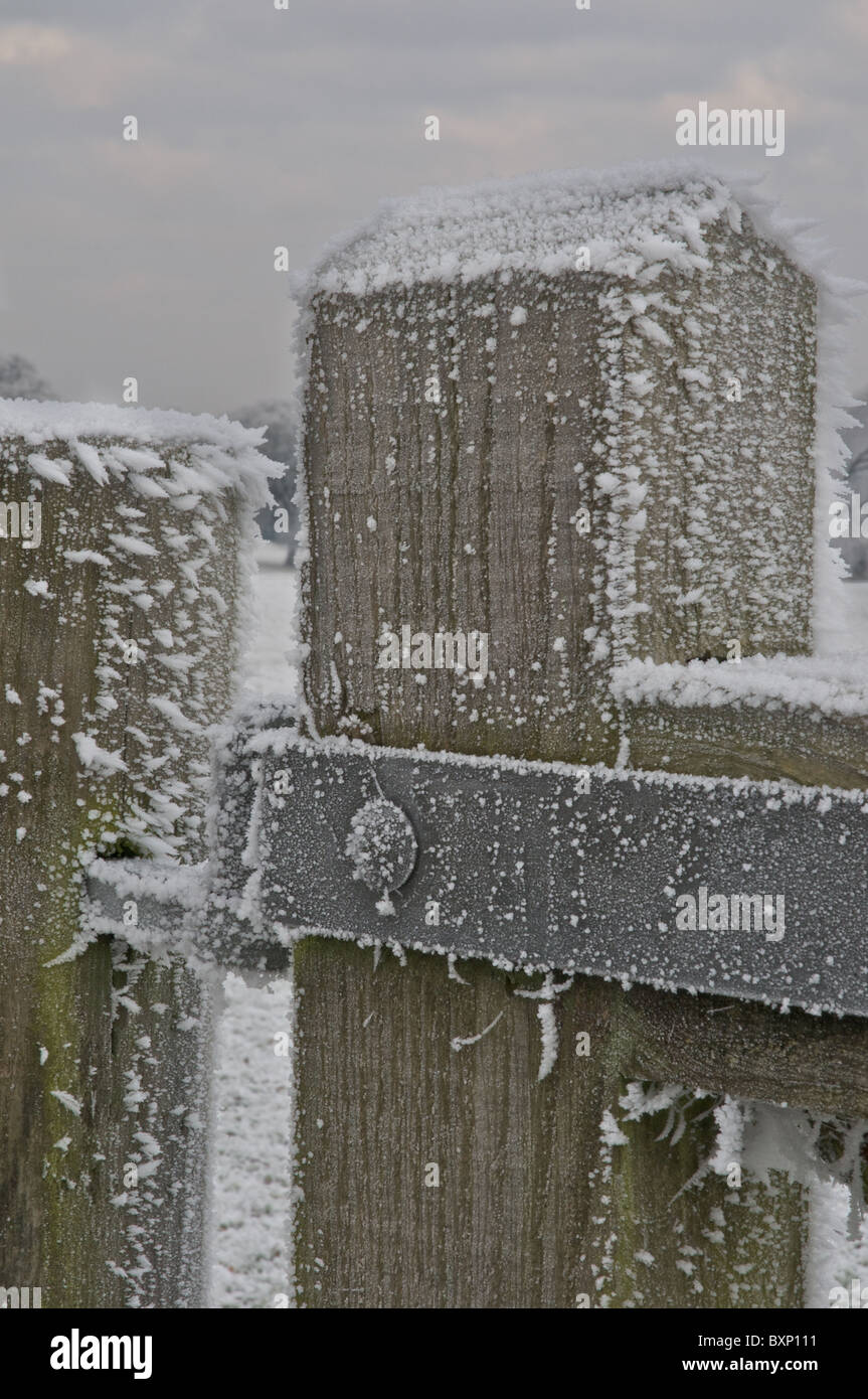Wintery ice grips a gatepost in the Lincolnshire countryside - Stock Image