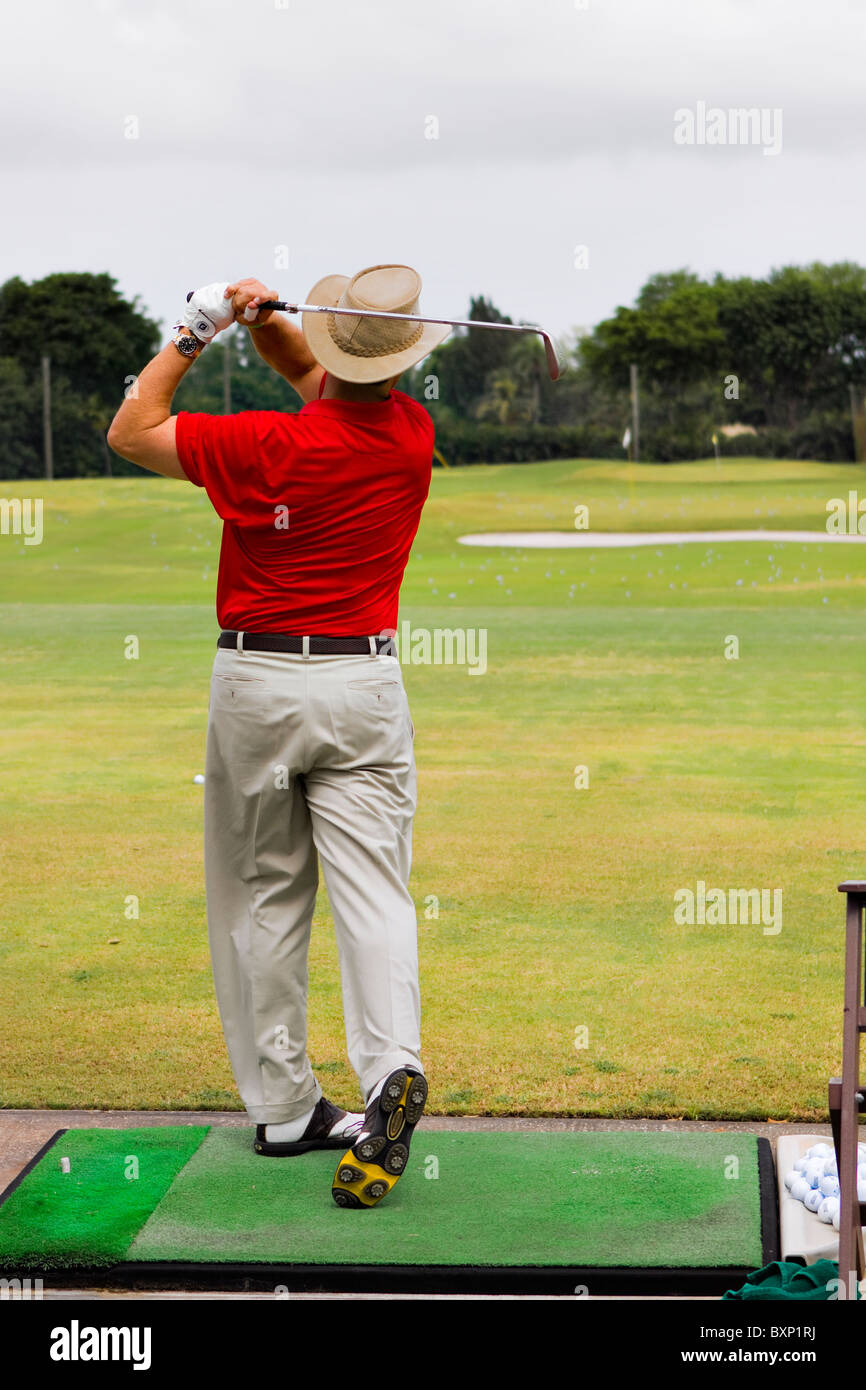 man with hat and red shirt on the golf driving range - Stock Image