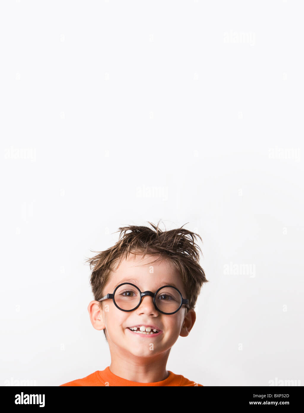 Image of happy child with tousled hair looking at camera with smile - Stock Image