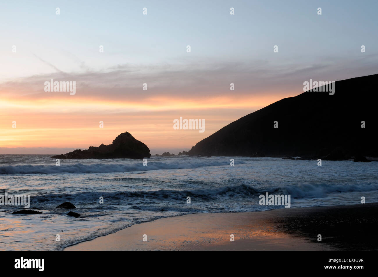 Crashing waves and sea stack at sunset on Pfeiffer beach along the Big Sur coast, Pacific Highway one 1 California - Stock Image