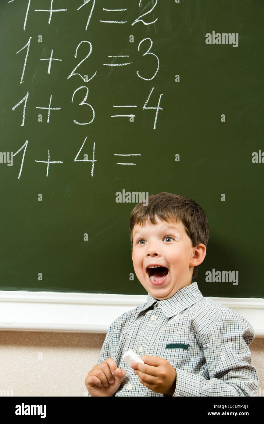 Portrait of happy boy screaming before blackboard with sums on it during lesson - Stock Image