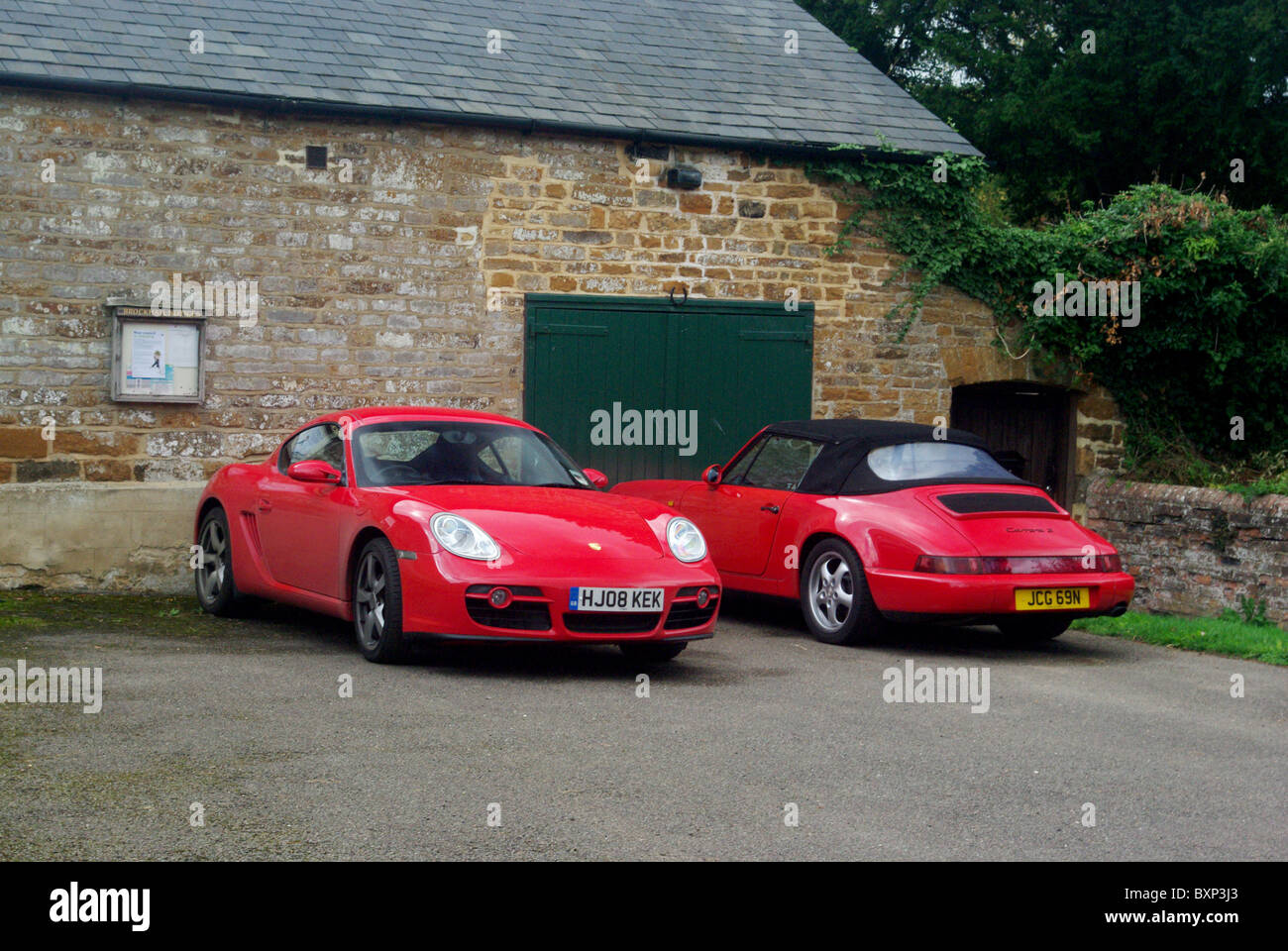 Two red Porsche sports cars outside the village hall, Brockhall, Northamptonshire, UK - Stock Image