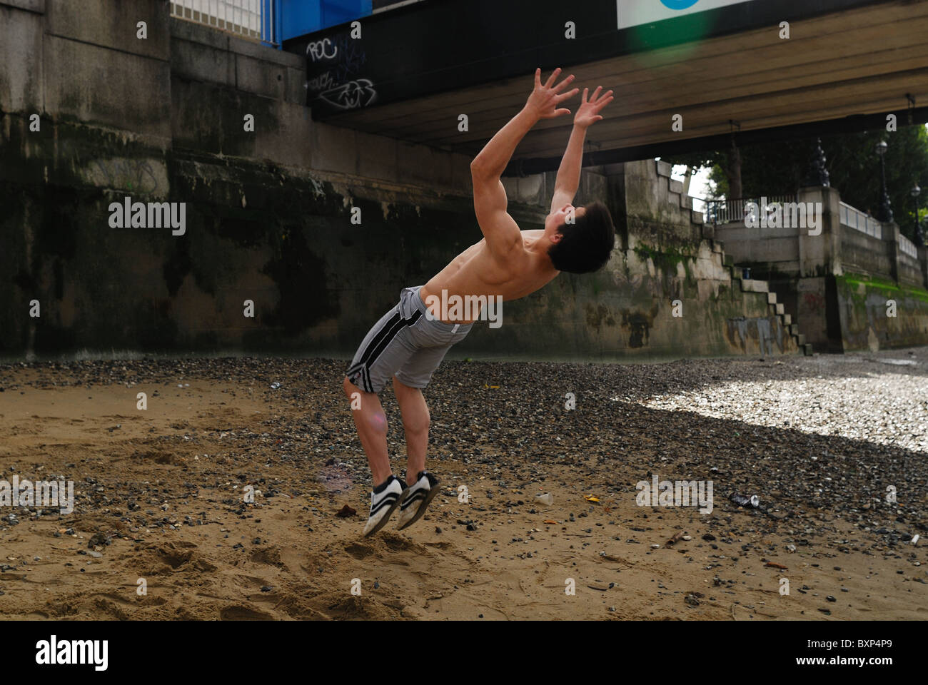 Traceur practicing the art of Parkour along bank of River Thames in London. - Stock Image