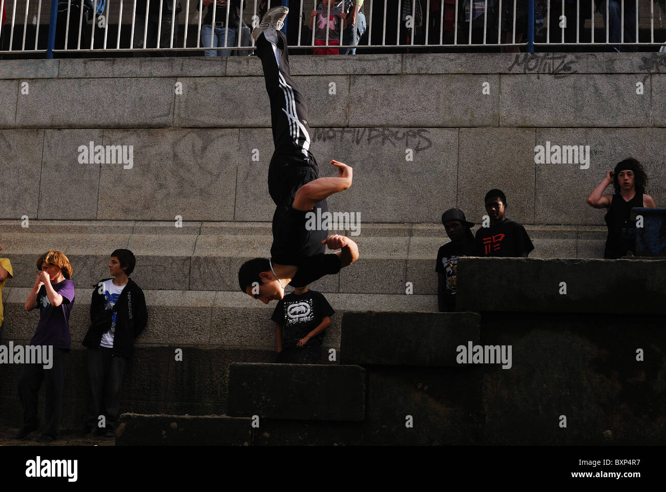 Traceur practicing the art of Parkour doing flip from steps along bank of River Thames in London. - Stock Image