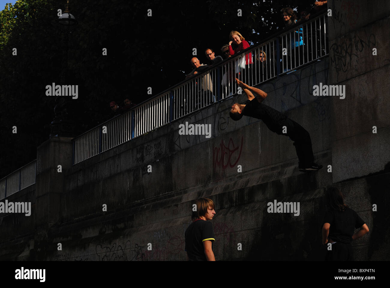 Traceur practicing the art of Parkour doing backflip from wall along bank of River Thames in London. - Stock Image