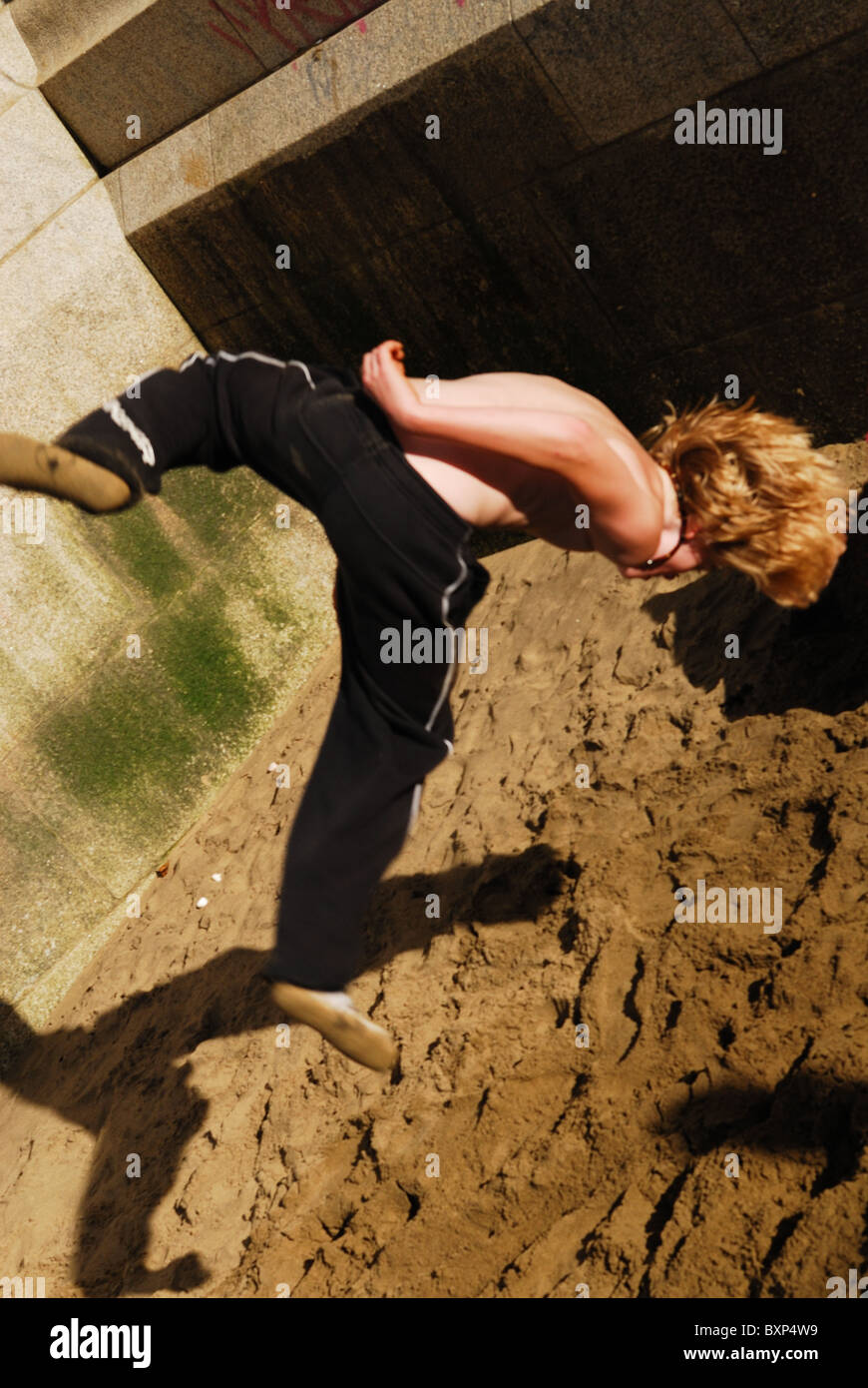Traceur practicing the art of Parkour on the bank of the River Thames in London. - Stock Image