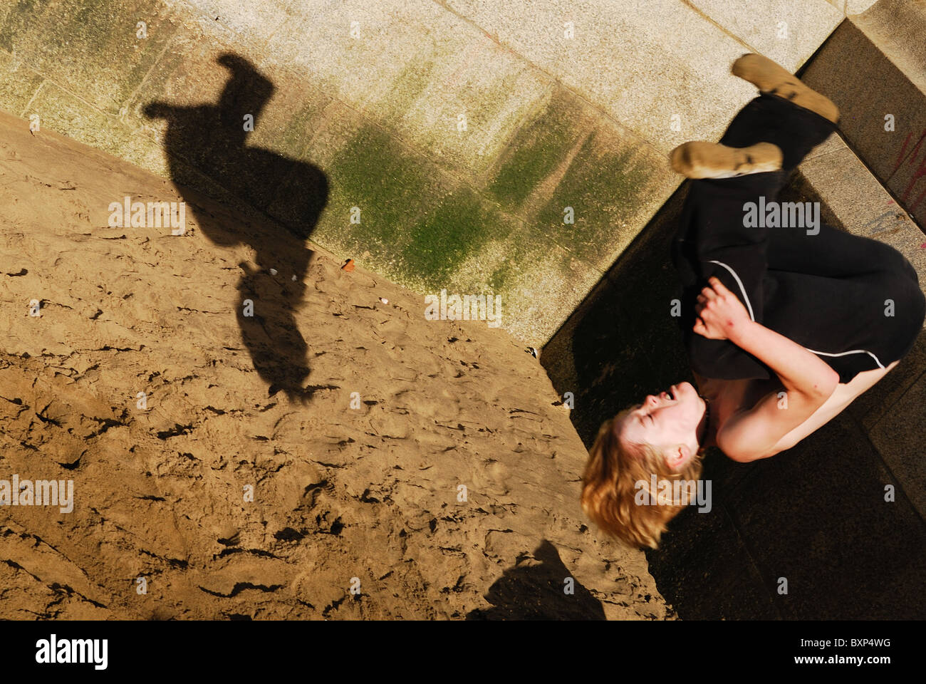 Traceur practicing the art of Parkour doing flips on the banks of the River Thames in London. - Stock Image