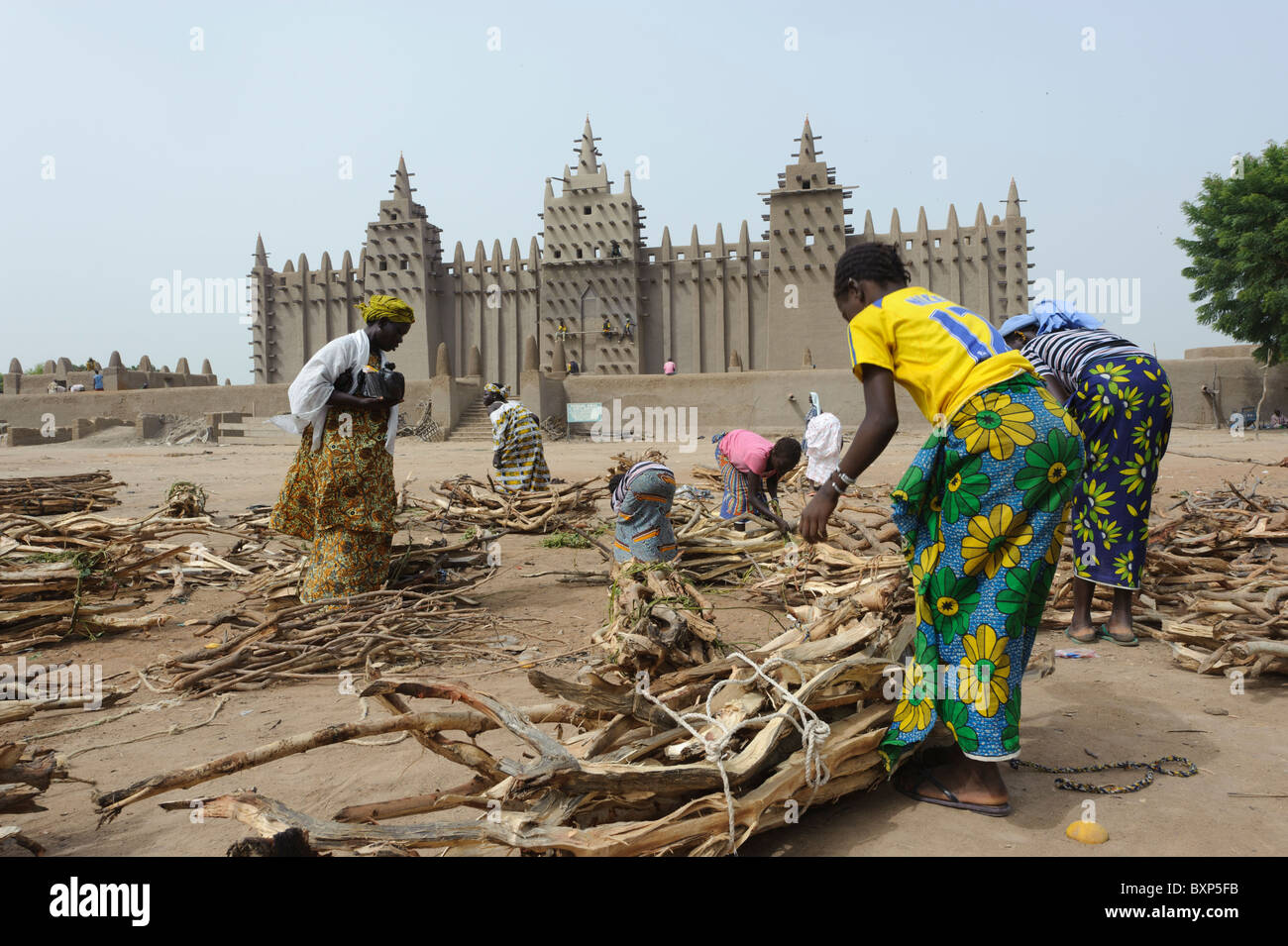 Fulani women gathering fire wood in front of the Great  Mosque of Djenné, Mali - Stock Image