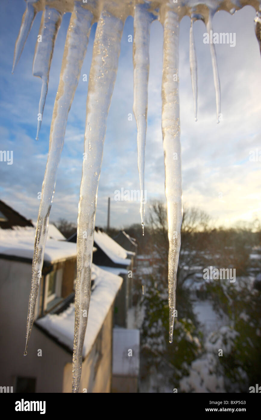 Large icicles hanging in front of a window, down from the roof. Wintertime. Stock Photo