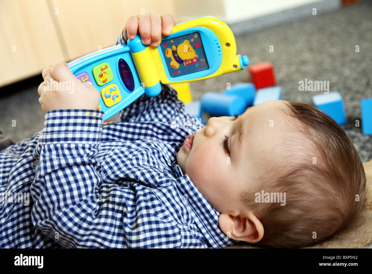 6 month old little boy laying in his children room, on a blanket, smiling, looking happy and friendly. Playing with Stock Photo