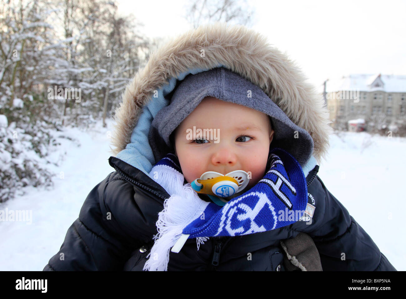 6 month old little boy on the back of his mother, on a walk  in winter, snow, smiling, looking happy and friendly. - Stock Image