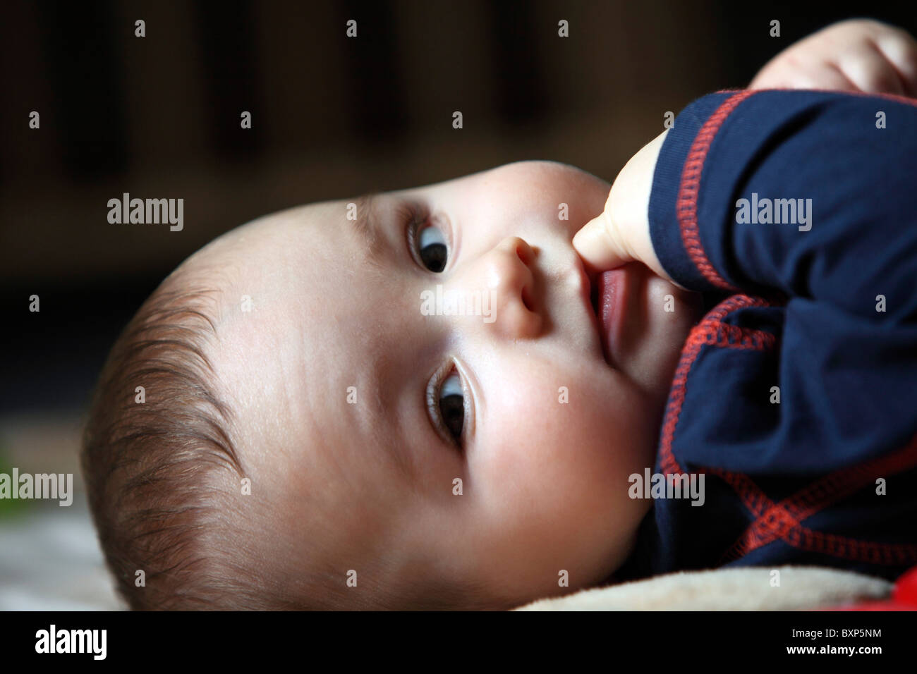 6 month old little boy laying in his children room, on a blanket, smiling, looking happy and friendly. Stock Photo