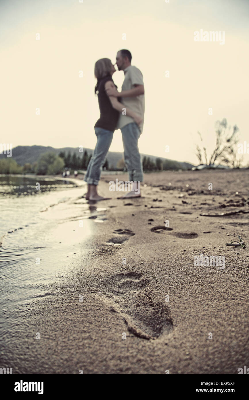 modern couple holding each other on beach with footprints in sand Stock Photo