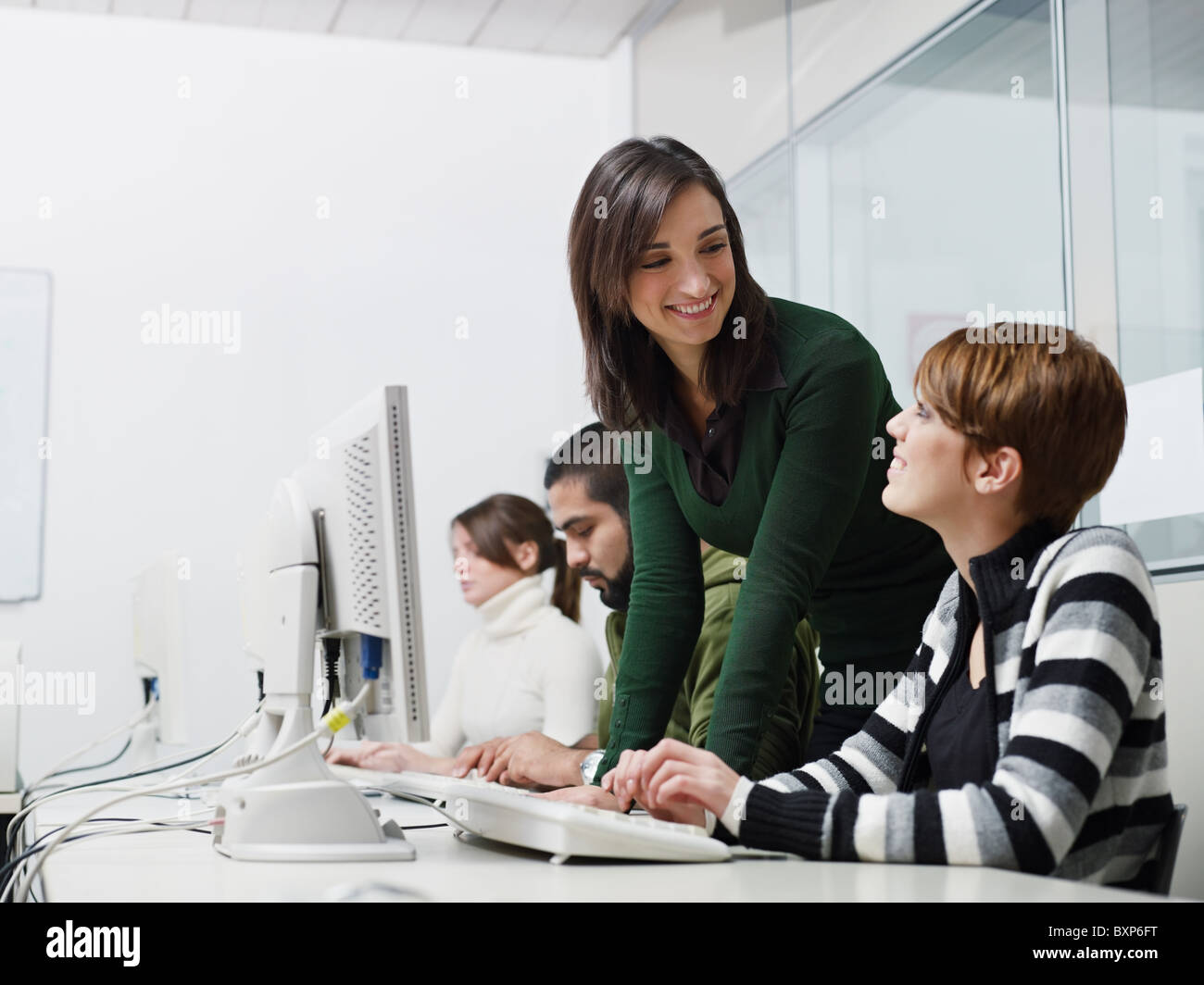Computer lab with caucasian female teacher helping student. Horizontal shape, side view, waist up, copy space - Stock Image