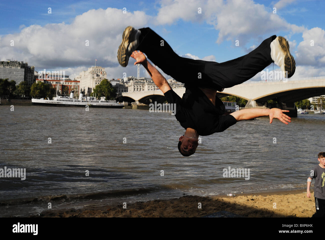 Traceur practicing the art of Parkour along the bank of the River Thames in London. - Stock Image