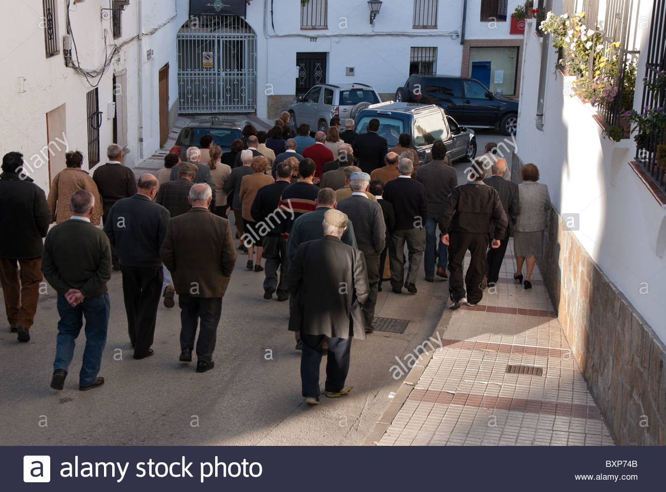 Mourners walk behind a hearse down a quiet side street in Gaucin, Spain. - Stock Image