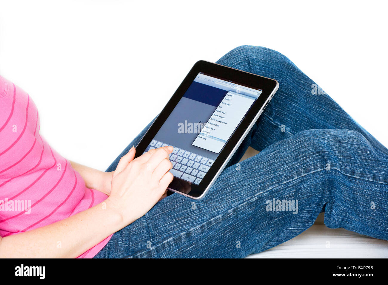 Woman relaxing using an Apple Mac iPad on her lap typing a search on the internet - Stock Image
