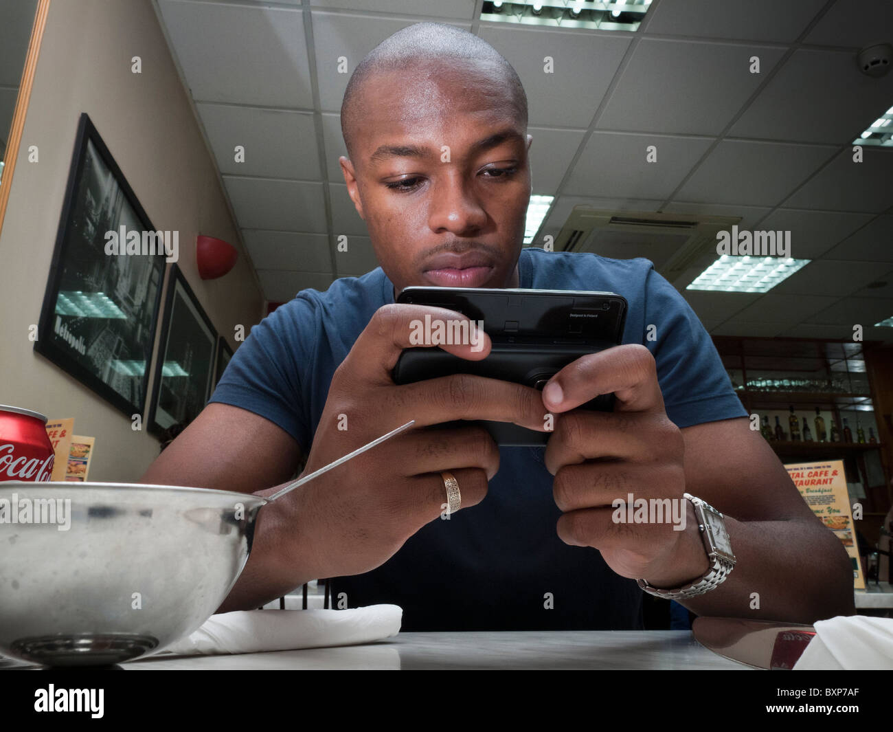 Man reading the news on the internet  on a smart mobile phone in a fast food restaurant - Stock Image