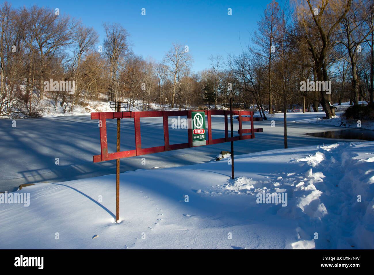 A thin ice sign warns visitors to the Pool in Central Park late in the afternoon on the day after a blizzard in - Stock Image