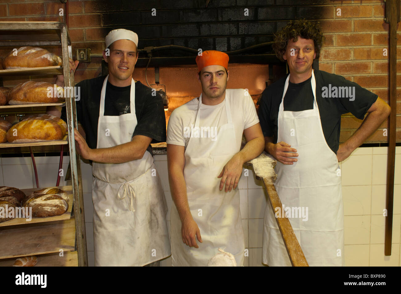 Artisan sourdough bakers in front of their Allan Scott designed woodfired oven - Stock Image