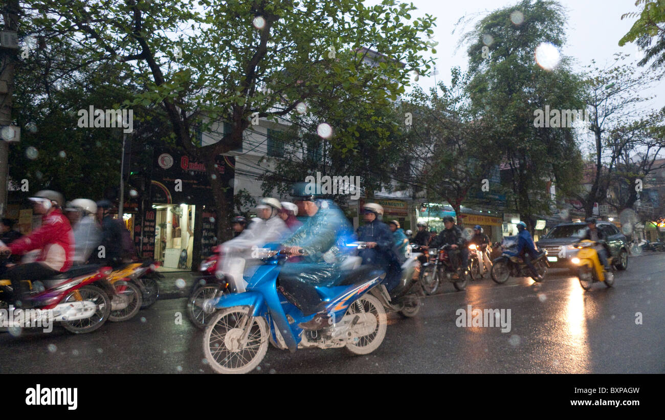 Motorscooters on a busy Hanoi street in the rain Stock Photo
