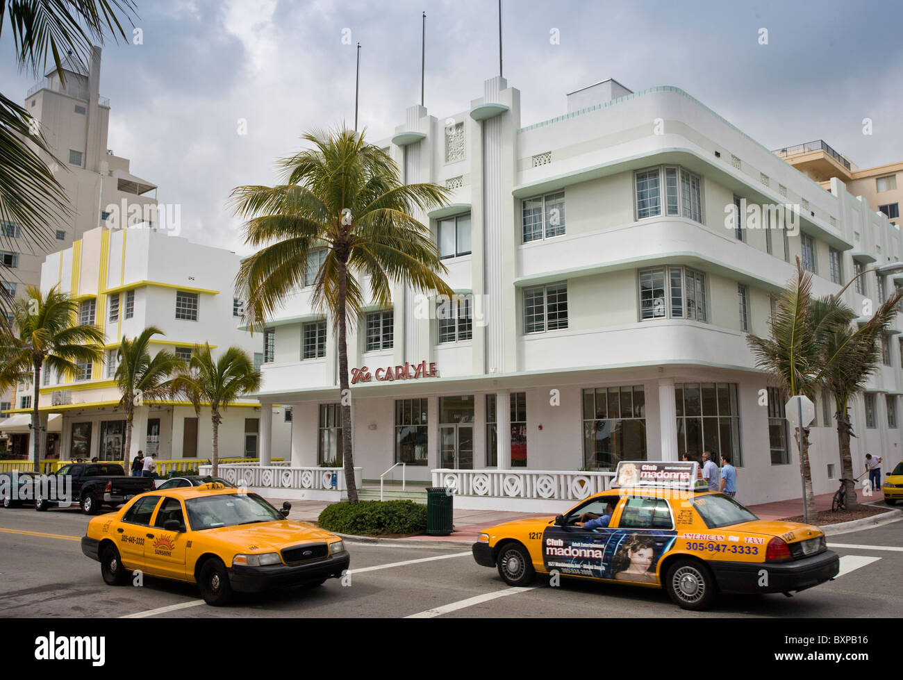 Yellow taxi cabs by The Carlyle condo on Ocean Drive, South Beach, Miami, Florida, USA - Stock Image