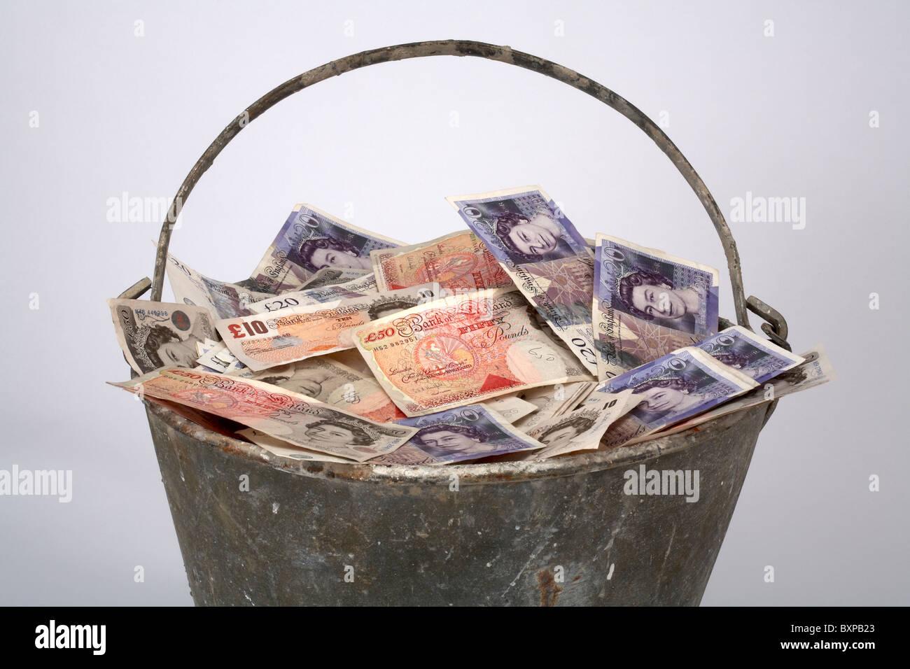 Metal Bucket full of English Currency - Stock Image