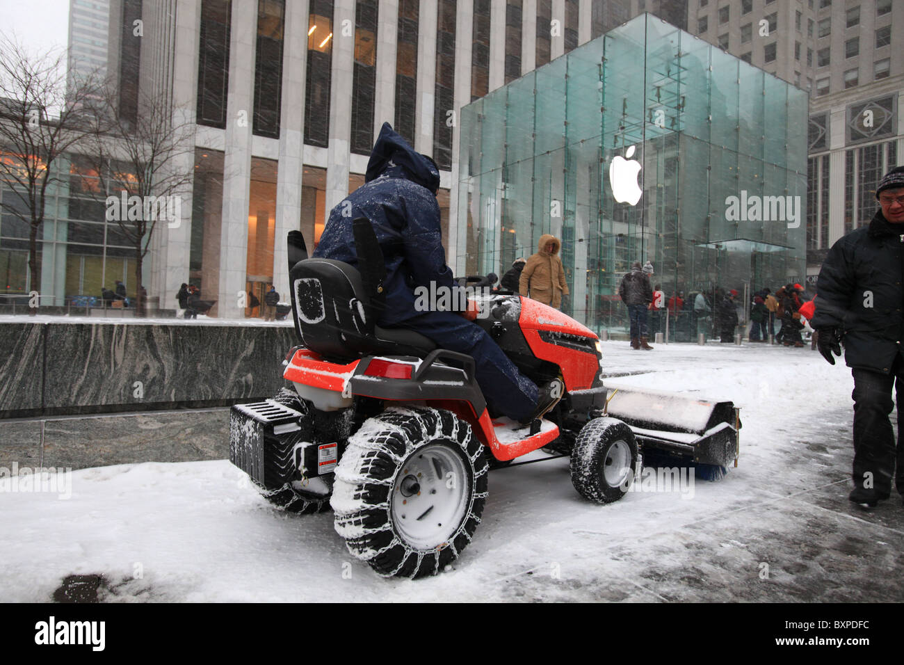 Snowplow clearing pavement on Fifth avenue outside Apple store, New York city, in record snowstorm in Christmas - Stock Image