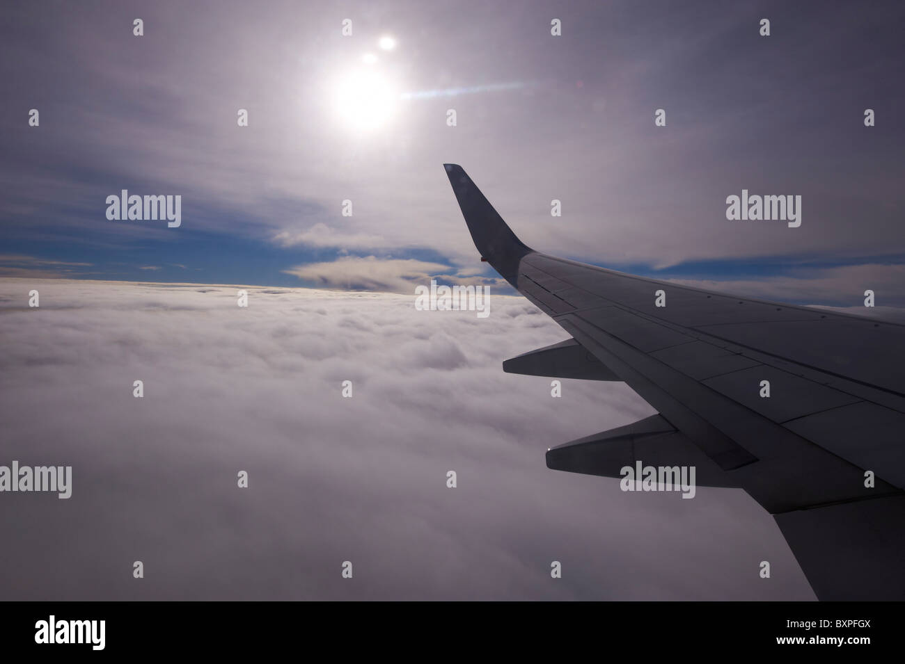 Looking out over clouds through airliner window Stock Photo