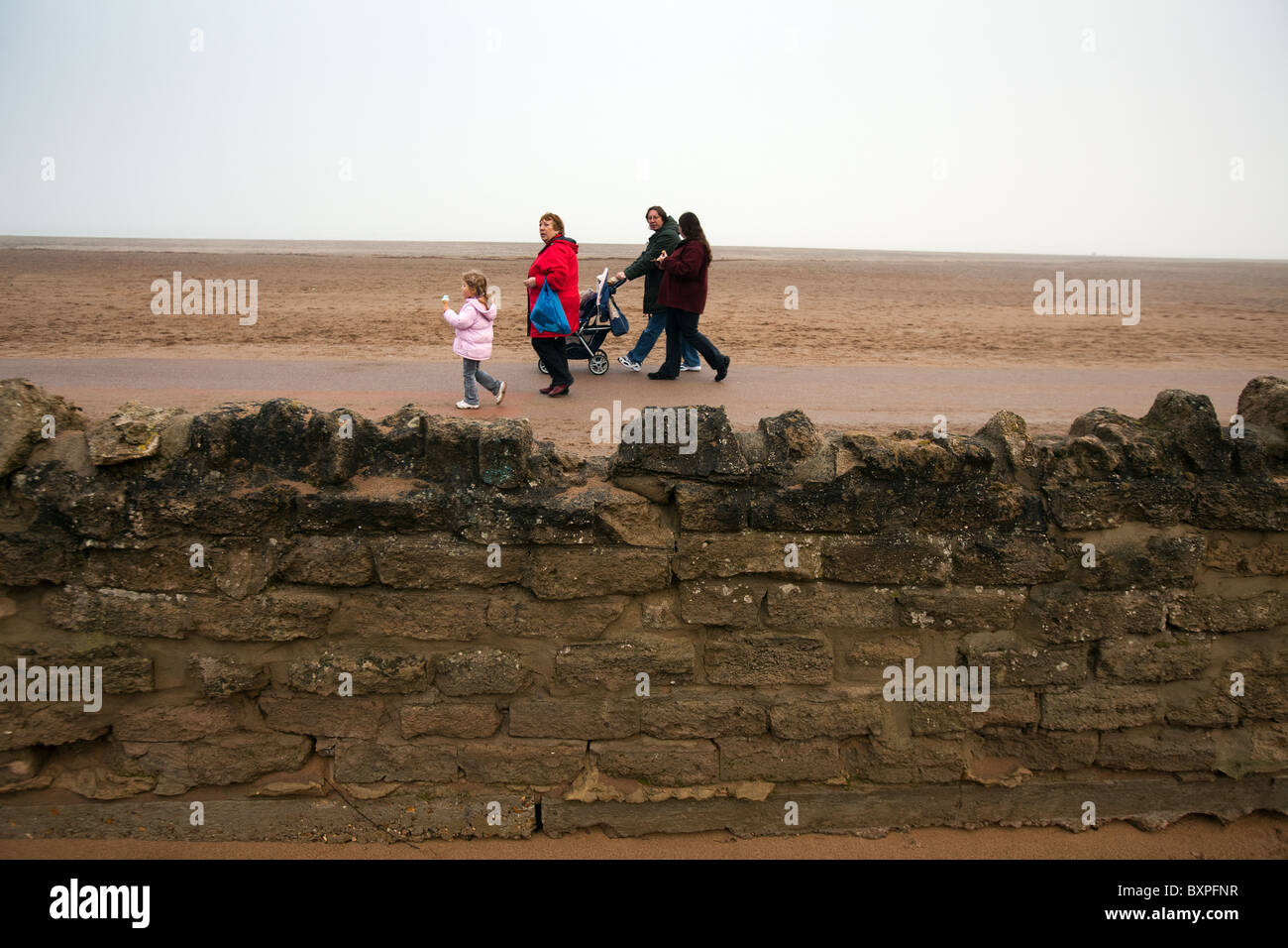 Skegness, Lincolnshire, UK.Skegness, Lincolnshire, UK. A family walk along the sea front promenade in misty weather. Stock Photo