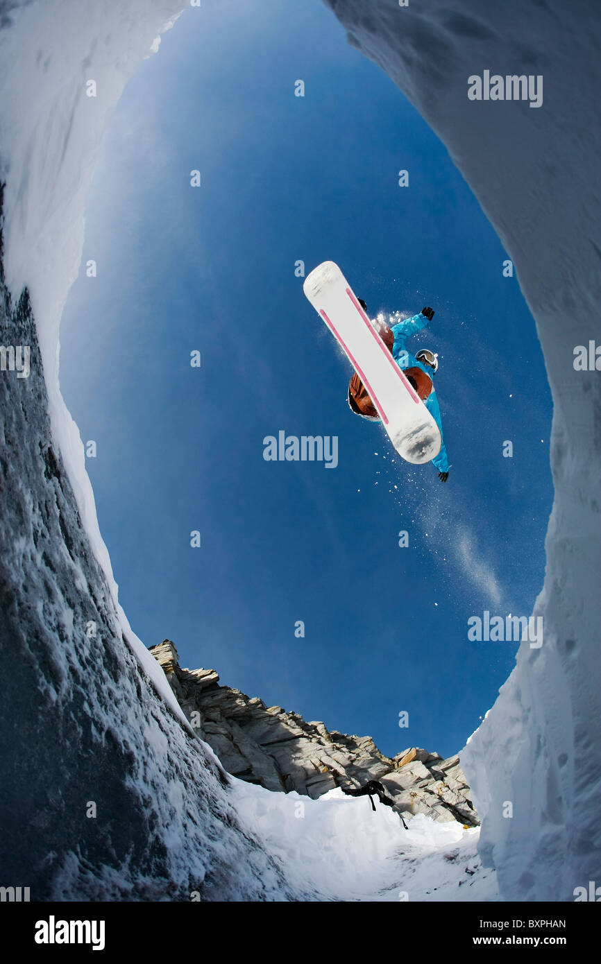 View from below of agile snowboarder in high jump over blue sky - Stock Image