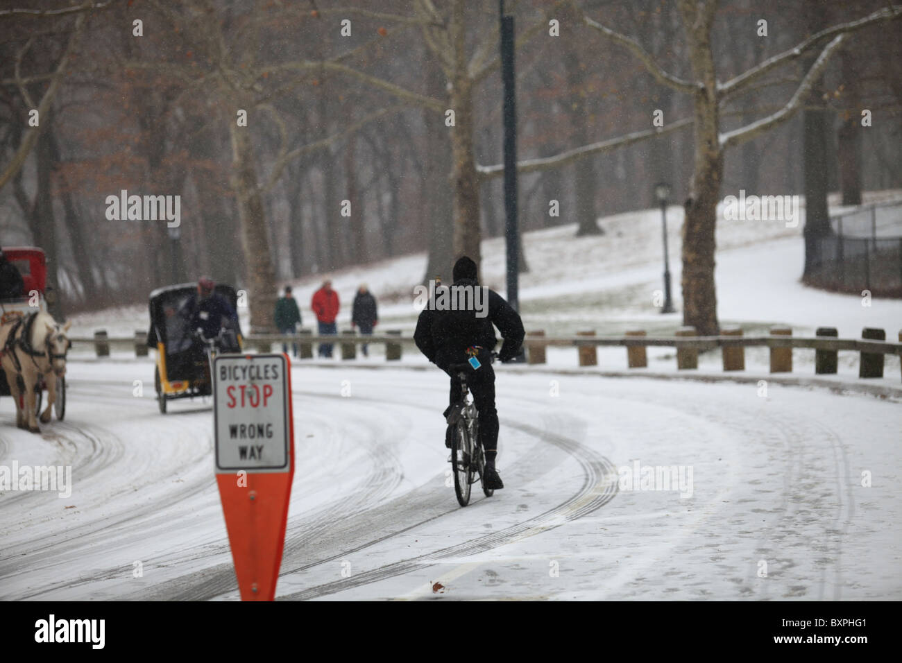 A bicycle going the wrong way down a small road in Central Park, New York city, in winter snowfall during Christmas - Stock Image