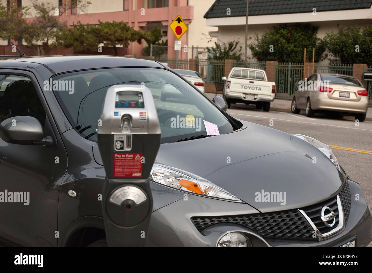 A car with a parking ticket issued due to an expired meter. - Stock Image