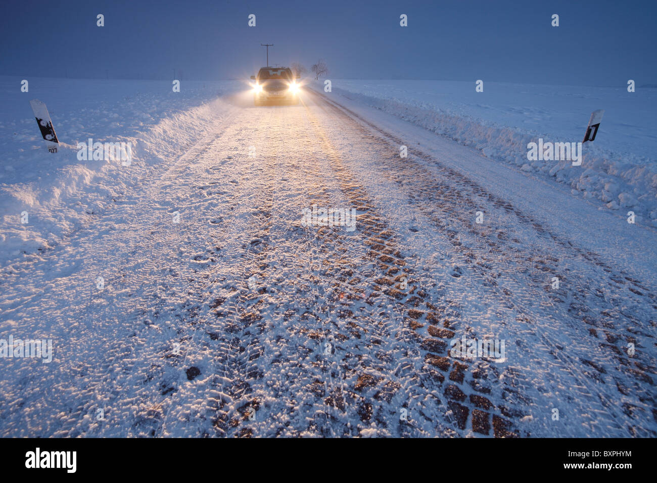 car (Toyota Avensis) on a snow-covered country road near Halle (Saale), Germany - Stock Image