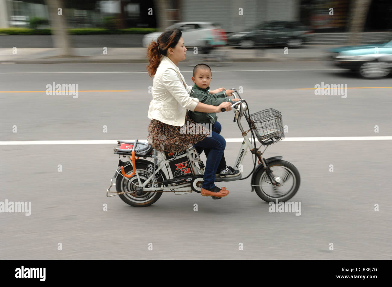 A woman and young child riding an electric scooter along a road in Yangzhou Jiangsu Province of China - Stock Image