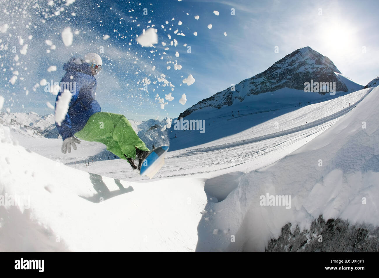 Photo of snowboarder over snowdrift going in for sport in winter - Stock Image